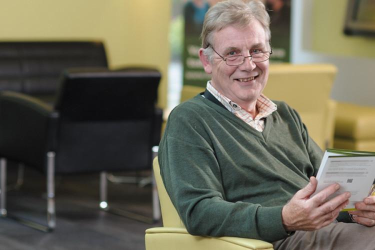 Older man sitting holding a leaflet, smiling at the camera