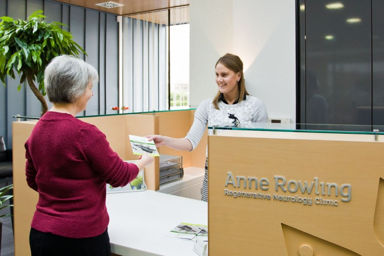 patient and receptionist talking at the clinic reception desk