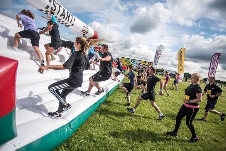 Gung Ho participants running onto an inflatable obstacle