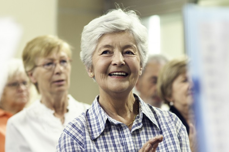 Older lady with white hair in an audience smiling