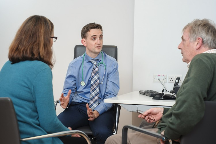 A doctor speaking to a patient and relative