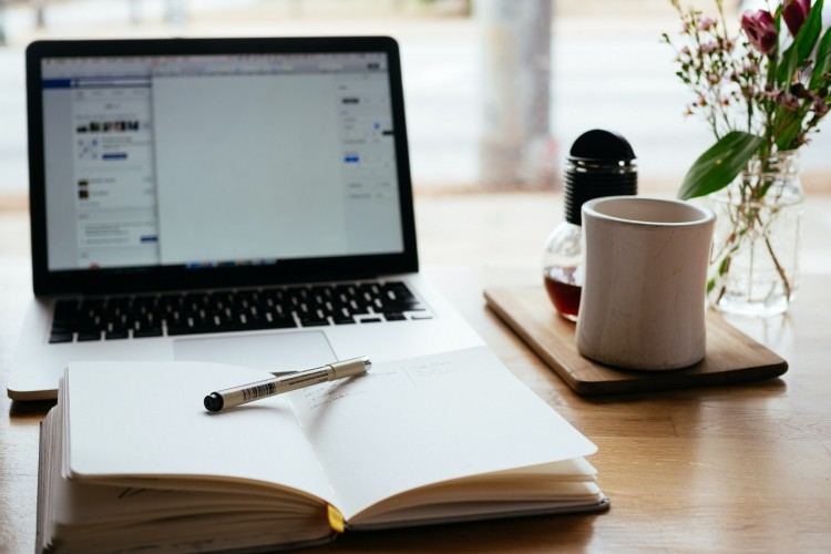laptop with notebook and cup of coffee