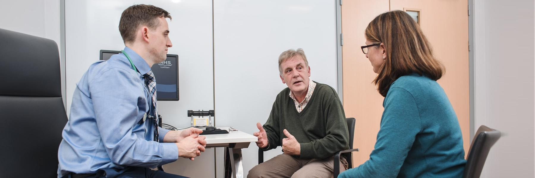 older male patient with friend chatting to a doctor in a clinic