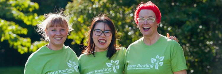 3 supporters smiling at the camera wearing green Anne Rowling Clinic T-shirts