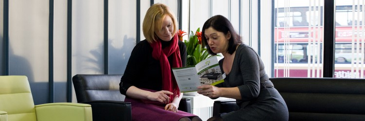 Two women sitting in the Anne Rowling Clinic looking at a leaflet together.