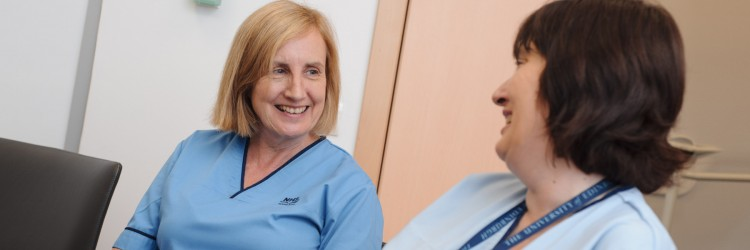Two nurses sat smiling and chatting with each other