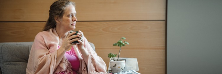 A woman sitting on a sofa, holding a mug and looking out of a window