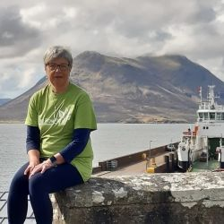 Ann Gillies sitting in front of a boat and loch